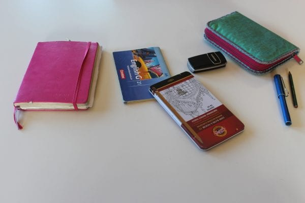 Die wichtigsten Utensilien aus Marcellas analogem Leben: Skizzenbuch, Vokabelheft, Stifte und das ausgeschaltete Tastenhandy.